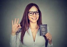 Donna felice con il passaporto di U.S.A. che dà segno giusto Fotografie Stock