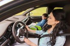 Donna felice con il piccolo bambino che guida in automobile Fotografie Stock Libere da Diritti