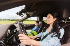 Donna felice con il piccolo bambino che guida in automobile Immagine Stock Libera da Diritti