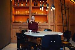 Donna felice con il sorriso stupefacente che chiama con il telefono delle cellule mentre sedendosi da solo nell'interno di lusso  Fotografia Stock Libera da Diritti
