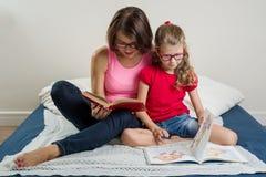 Donna felice con il suo bambino della figlia, leggente insieme un libro a Immagini Stock Libere da Diritti