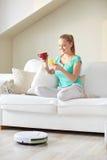Donna felice con il tè bevente dello smartphone a casa Fotografie Stock Libere da Diritti