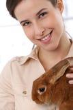 Donna felice con l'animale domestico del coniglietto Fotografia Stock