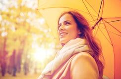 Donna felice con l'ombrello che cammina nel parco di autunno Fotografie Stock