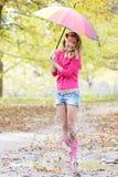 Donna felice con l'ombrello variopinto nel parco di autunno Immagine Stock