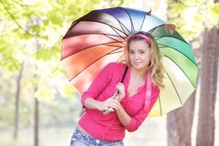 Donna felice con l'ombrello variopinto nel parco di autunno Fotografia Stock
