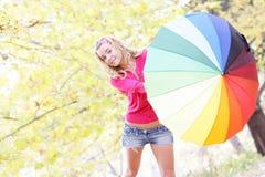 Donna felice con l'ombrello variopinto nel parco di autunno Fotografie Stock