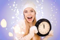 Donna felice con l'orologio contro le luci Immagine Stock Libera da Diritti