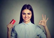 Donna felice con la carta di credito che mostra segno giusto Fotografia Stock