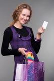 Donna felice con la carta di credito ed i sacchetti Immagine Stock Libera da Diritti