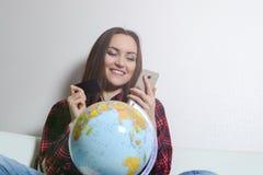 Donna felice con la carta di credito ed il telefono a disposizione, seduta sorridente sul sofà con il globo La gioia dei bigliett Fotografie Stock