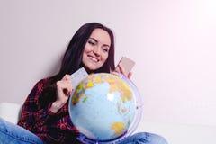 Donna felice con la carta di credito ed il telefono a disposizione, seduta sorridente sul sofà con il globo La gioia dei bigliett Fotografia Stock Libera da Diritti
