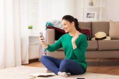 Donna felice con la mano d'ondeggiamento dello smartphone a casa fotografia stock