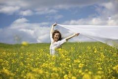 Donna felice con la parte del panno bianca in vento Fotografie Stock