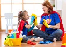 Donna felice con la stanza e divertiresi di pulizia del bambino gioco a casa Concezione di lavoro domestico della famiglia fotografia stock libera da diritti