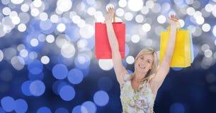 Donna felice con le armi alzate tenendo i sacchetti della spesa immagine stock libera da diritti