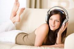 Donna felice con le cuffie sul sofà in salotto Fotografie Stock
