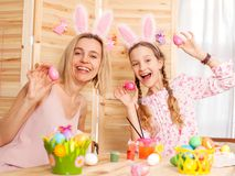 Donna felice con le uova di Pasqua della pittura del bambino Immagini Stock