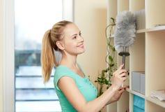 Donna felice con lo spolveratore che pulisce a casa Immagini Stock