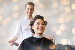 Donna felice con lo stilista che fa pettinatura al salone immagine stock libera da diritti