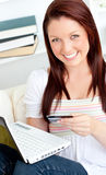 Donna felice con una carta di credito e un computer portatile Fotografia Stock