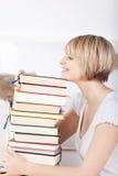 Donna felice con una pila enorme di libri Immagine Stock