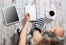 Donna felice con una tazza di caffè, un blocco note e una compressa Fotografie Stock