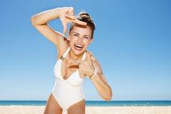 Donna felice in costume da bagno bianco all'inquadratura della spiaggia sabbiosa con le mani Fotografie Stock