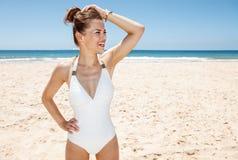 Donna felice in costume da bagno bianco alla spiaggia sabbiosa che guarda da parte Immagini Stock Libere da Diritti