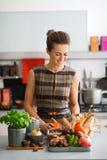 Donna felice in cucina che esamina giù le verdure di autunno Fotografia Stock Libera da Diritti