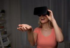 Donna felice in cuffia avricolare o vetri di realtà virtuale Immagine Stock