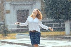 Donna felice dai capelli rossi nella pioggia fotografia stock