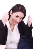 Donna felice davanti al suo computer portatile all'ufficio immagini stock libere da diritti