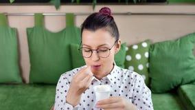 Donna felice dei pantaloni a vita bassa del primo piano medio giovane che mangia il dessert cremoso fresco naturale del yogurt fa video d archivio