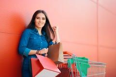 Donna felice del cliente con il carrello davanti al deposito Immagini Stock Libere da Diritti