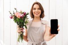 Donna felice del fiorista che sta con i fiori che mostrano esposizione del telefono cellulare Fotografia Stock Libera da Diritti