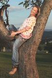 Donna felice del paese che si siede in un albero per una rottura Fotografie Stock