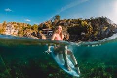 Donna felice del surfista al surf con la mano di shaka Il surfista si siede al bordo in oceano fotografia stock libera da diritti
