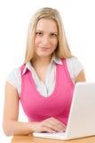 Donna felice dell'adolescente che si siede alla tabella con il computer portatile Immagine Stock