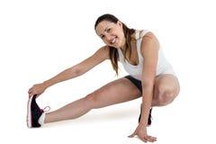 Donna felice dell'atleta che allunga il suo tendine del ginocchio Fotografia Stock Libera da Diritti