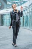 Donna felice dell'ufficio che cammina fuori della costruzione Immagini Stock