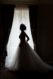 Donna felice della bella sposa sexy delicata con una corona sulla sua testa dalla finestra con un grande mazzo di nozze in un bia Fotografia Stock