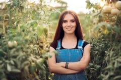 Donna felice della campagna fiera del suo giardino di verdure della serra Immagini Stock