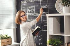 Donna felice della donna di affari al consiglio scolastico con pianificazione di programma Immagini Stock