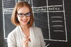 Donna felice della donna di affari al consiglio scolastico con pianificazione di programma Fotografia Stock