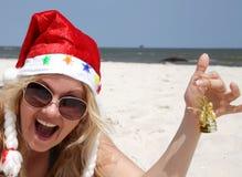 Donna felice della Santa con il segnalatore acustico sulla spiaggia Immagini Stock