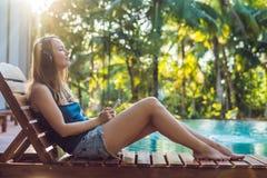 Donna felice dello smartphone che si rilassa vicino alla piscina che ascolta con i earbuds il flusso continuo della musica Bella  fotografia stock libera da diritti