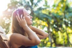 Donna felice dello smartphone che si rilassa vicino alla piscina che ascolta con i earbuds il flusso continuo della musica Bella  fotografie stock