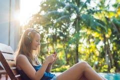 Donna felice dello smartphone che si rilassa vicino allo spirito d'ascolto della piscina Fotografie Stock Libere da Diritti