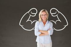 Donna felice dello studente con il grafico dei pugni che sta contro la lavagna grigia Fotografia Stock